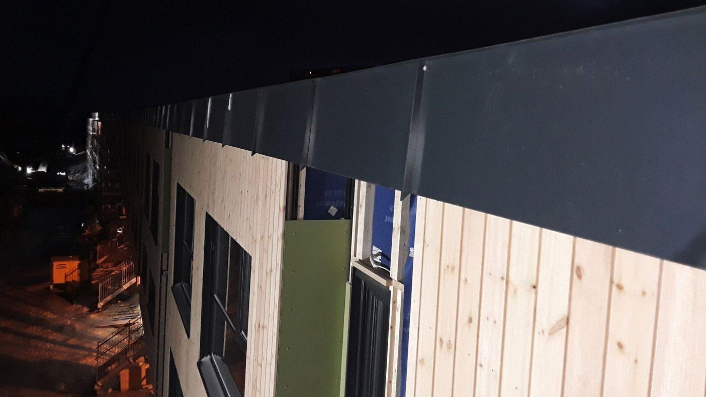 I mørket jobber blikkenslagerne med å legge beslag og annet på bygget som nærmer seg ferdig.